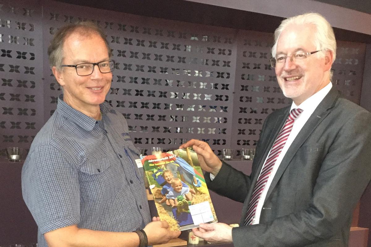 Herr Pfeifer überreicht Den Neuen Jahresbericht An Herrn Michael Bammessel