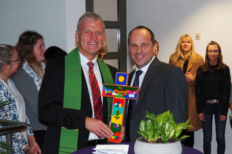 Dekan Peter Bertram (links) überreicht Vorstand Andreas Karau Ein Kreuz Für Die Neue Geschäftsstelle.